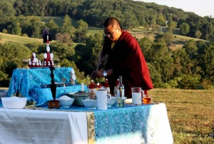 Ven. Acarya Namdrol Gyatso preparing the shrine.