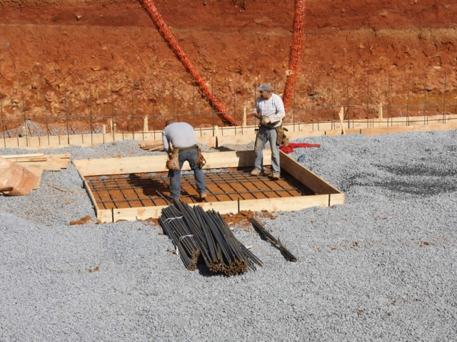 Workers place reinforcing steel bars (rebar) into a pier which will eventually support an important vertical beam.
