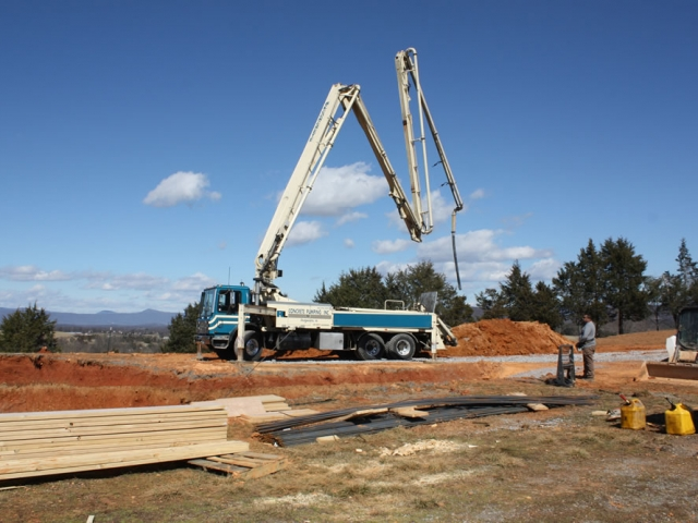 The concrete pumping truck arrives at the temple site.  It is waiting for the arrival of a cement mixer to which it will link, then pumping cement through a hose which is moved and positioned for the pouring of the cement into the construction site.