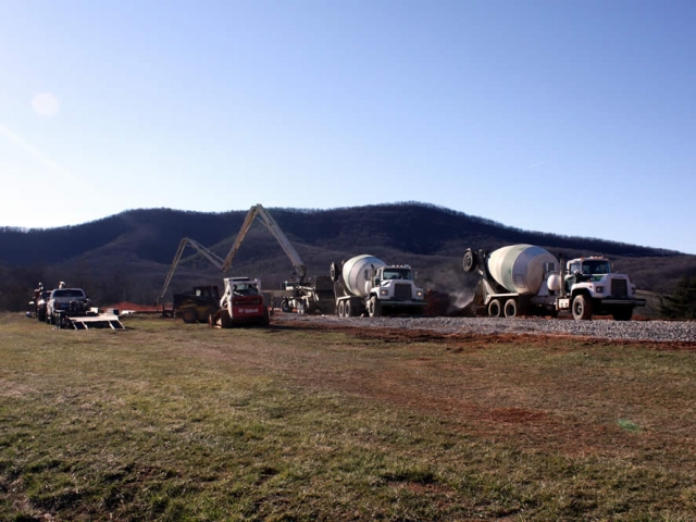 Cement trucks arrive at the work site. It will take 10 cement trucks filled with cement to pour the footers and piers.