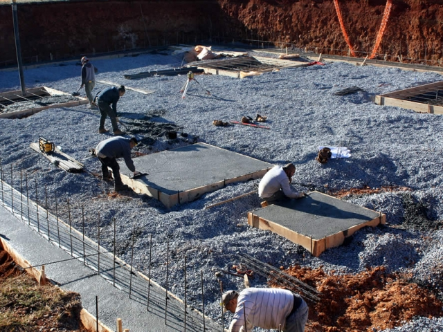 Workers hurry to smooth the concrete surfaces. Note: The small square area will support the elevator shaft.