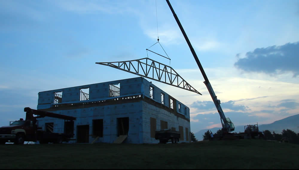 JULY 14-At dawn, first west roof truss is lifted into position.