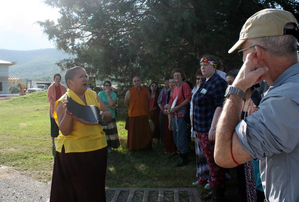 Jetsün Khandro Rinpoche shows sangha members a sample of the Japanese clay roof tiles.