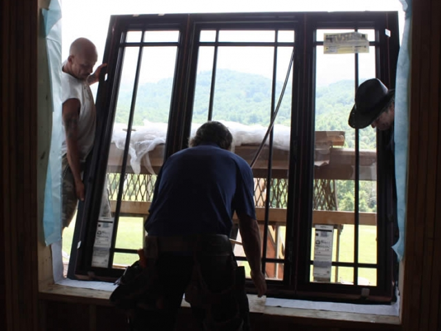 AUGUST 1-interior view of workers installing a window