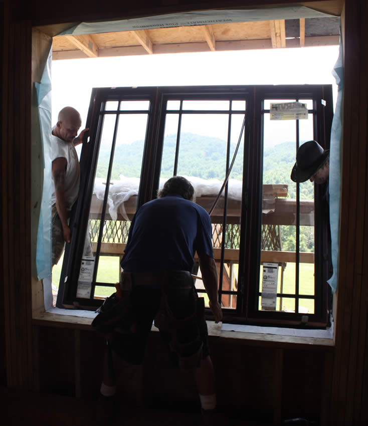 Workers install a window on the second floor.