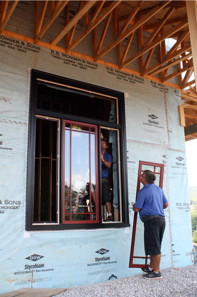 AUGUST 25-Workers install windows into frames. The transom at the top will provide more light and open to allow the circulation of fresh air.
