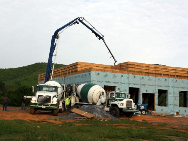 3 MAY—Cement mixer and pumper truck pour concrete for temple's second floor.