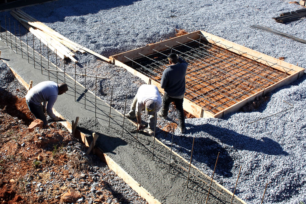 Workers smooth concrete in the footers.