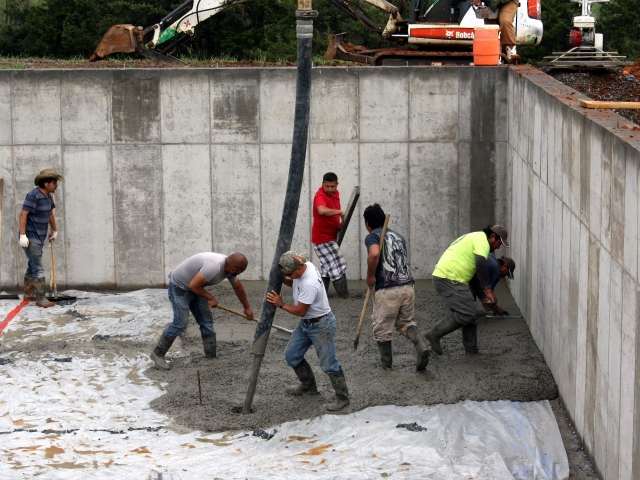 May 2-Workers applying the concrete from the hose and smoothing the surface.