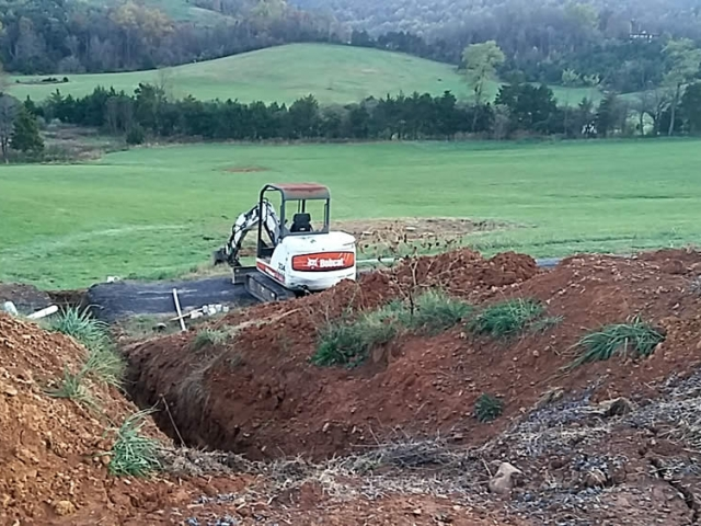 NOVEMBER 16-Preparing to lay lines for the septic system. Septic field in the distance.
