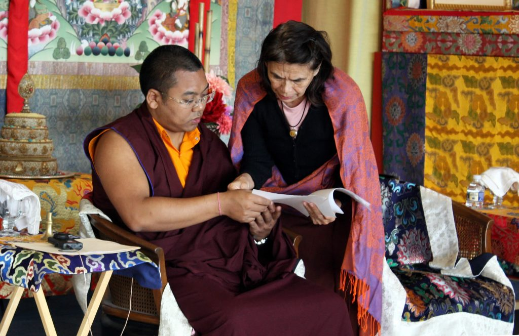 Ven. Acarya Namdrol Gyatso works with a student during Tibetan language class