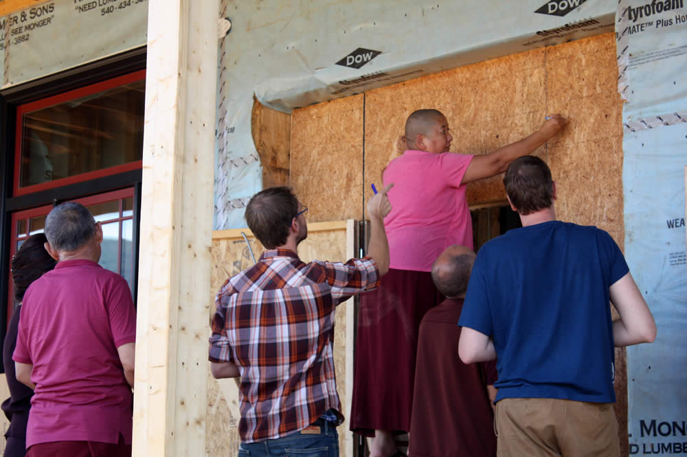 Jetsüun Khandro Rinpoche taking measurements for architectural features which will surround the temple doors.