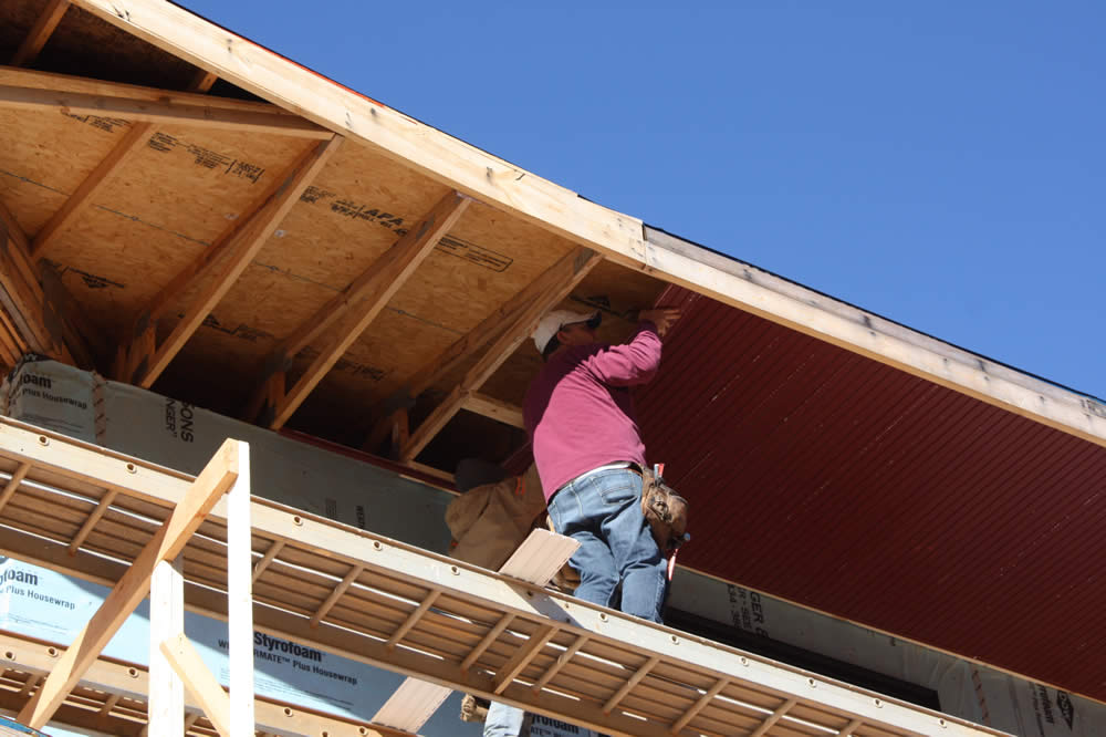 Workers begin installing soffits to the undersides of the overhanging eaves.