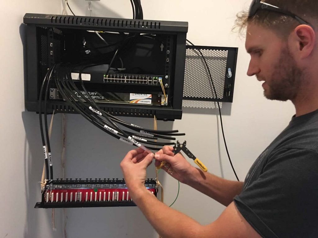 Alex Ryan prepares Cat6 cable in the network server rack.