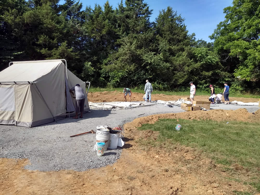 Setting up rental tents in a newly prepared area.