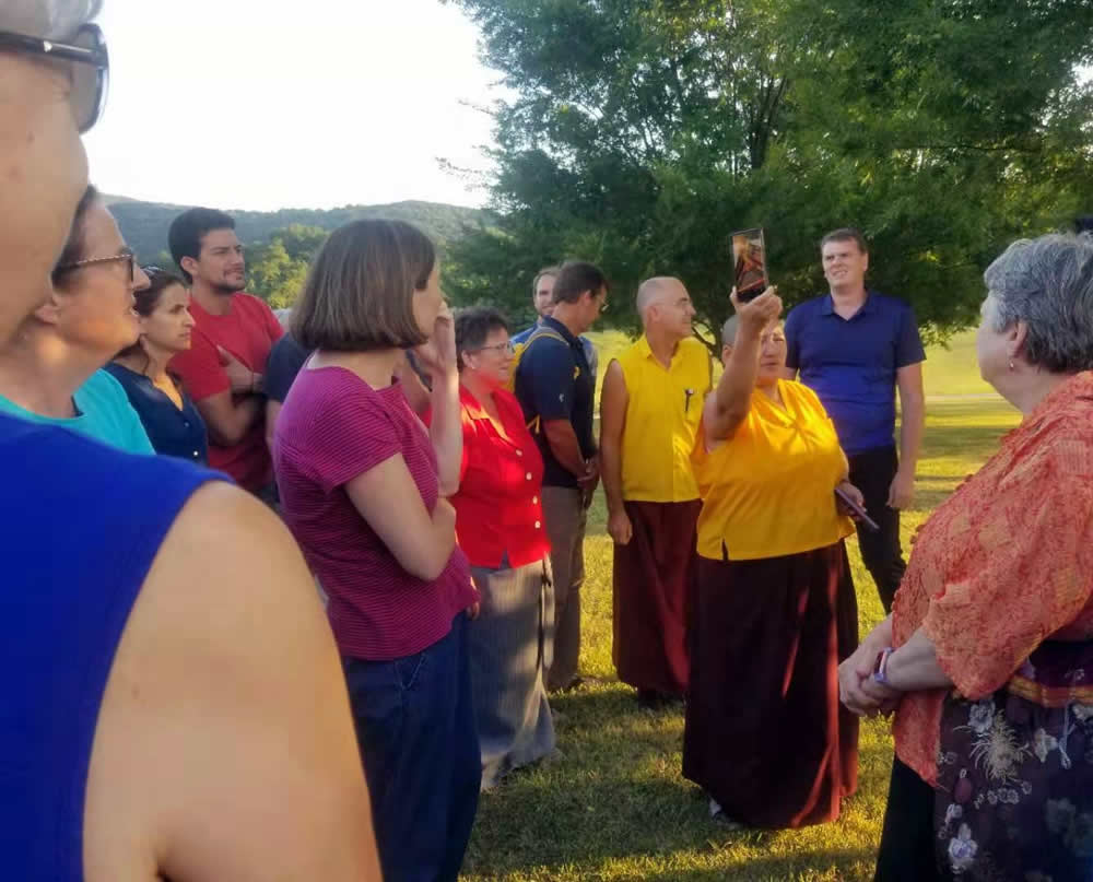 Rinpoche and sangha members gather near the new temple for a tour