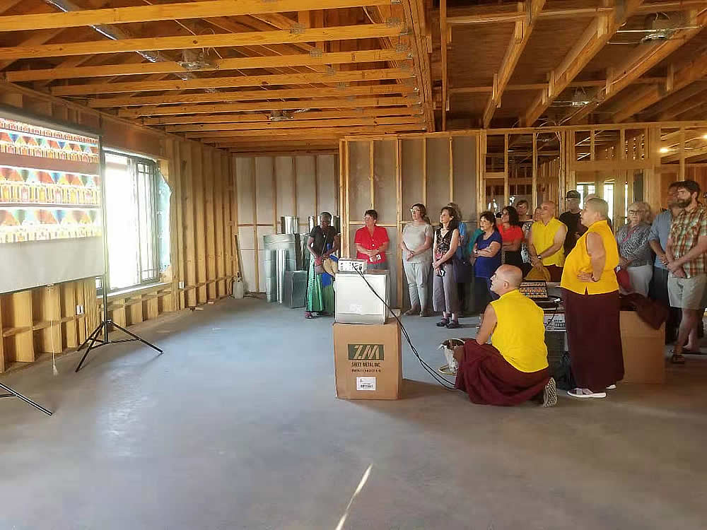 Rinpoche and sangha members visit the temple site and see images of the new door frames enroute from India